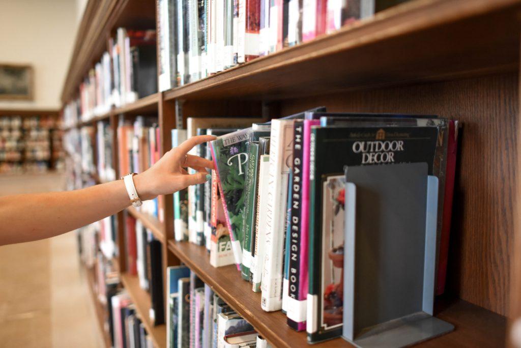 Main qui prend un livre dans une bibliothèque